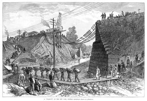 RAILROAD WASHOUT, 1885. Men and women walking across a footbridge due to a washed-out