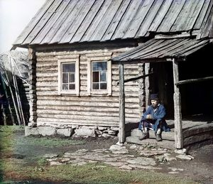 RUSSIA: LOG CABIN, 1910. A Bashkir man sitting on the steps of a log cabin in the