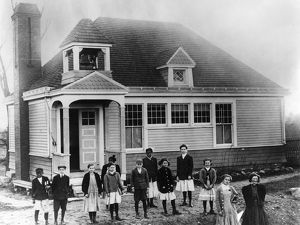 SCHOOLHOUSE, c1910. Black and white children outside of an American schoolhouse