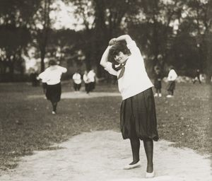 SOFTBALL GAME. A woman on the pitcher's mound preparing to throw the ball during