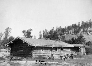 SOUTH DAKOTA: LOG CABIN. Five men sitting in the grass in front of an old log cabin