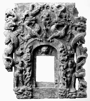Stone relief work from the front of a Buddhist shrine, depicting dragons, lions, and guardians