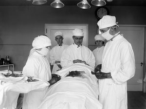 SURGERY, 1922. Surgeons at work in an operating room. Photograph, 1922