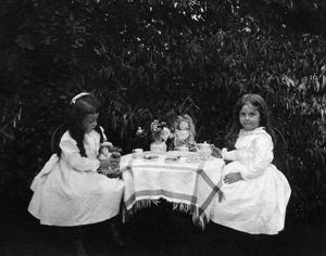 TEA PARTY, c1900. Two girls having a tea party with their dolls in a garden. Photograph