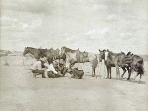 TEXAS: COWBOYS, c1907. Five cowboys gathered together as one of them draws a map