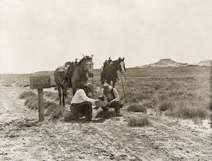 TEXAS: COWBOYS, c1907. Two cowboys reading mail next to a 'USM' postbox near the