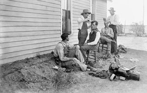 TEXAS: COWBOYS, c1908. Five cowboys outdoors with two of them getting haircuts