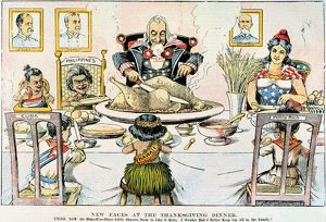 THANKSGIVING CARTOON, 1898. New Faces at the Thanksgiving Dinner: American cartoon, 1898, on the U