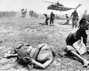 Viet Cong prisoners await transportation by helicopter after having been captured