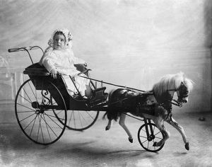 Vinson Walsh McLean, son of American heiress and socialite Evalyn McLean, sitting in a toy horse and carriage. Photograph, 1911.