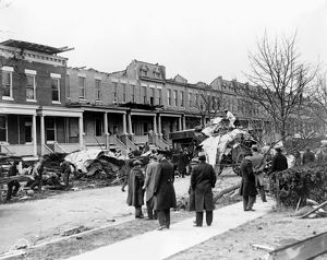 WASHINGTON, D.C.: HOUSES. Men on a sidewalk watching debris being cleaned up in