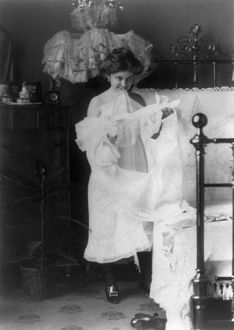 fashion/woman nightgown c1900 woman putting nightgown