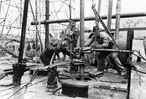 Workers loosening sections of pipe with clamps at an oil well in Kilgore, Texas