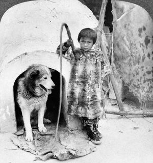 WORLD'S FAIR: ESKIMOS. An Eskimo boy and his dog standing outside an artificial