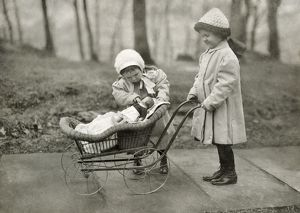 Two young girls playing with a Campbell Kid Doll and a baby carriage in New York City. Photograph by Lewis Hine, March 1912.