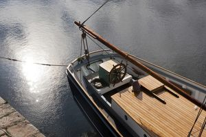 Pale autumn sunlight on the surface of water beside at tallship in the harbour at