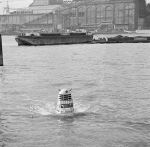 A Dalek emerges from the river Thames at the jetty near Battersea Church Road