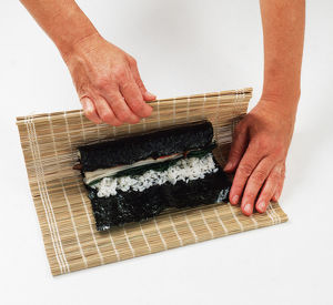 2 - Use the mat to help roll the nori round the rice