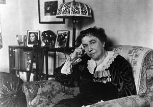 Ambassador alexandra kollontai at her home in moscow, on the bookshelf behind her