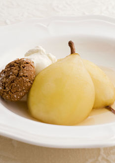 Two baked pears in Marsala with amaretti biscuits and whipped cream, close-up