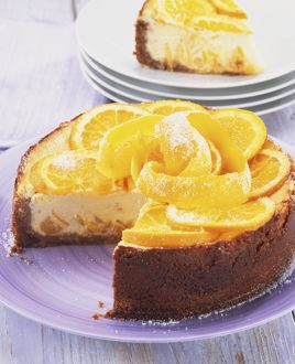 Baked St Clement's cheesecake, topped with slices of orange and lemon and strips of orange