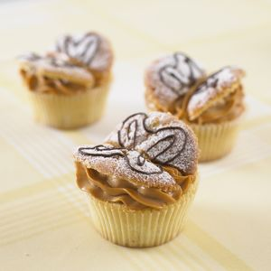 Banana cakes with dulce de leche icing and butterfly shaped decoration, close-up