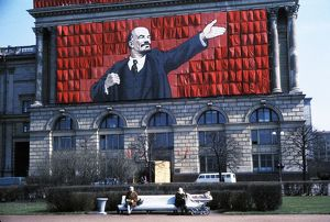 A banner of lenin on the side of a building overlooking two elderly women sitting