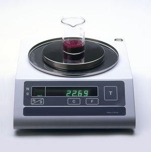 Beaker containing cobalt chloride, being weighed with digital scales