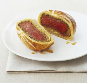 Beef Wellington, cut in two halves, showing rare-cooked fillets inside pastry parcels