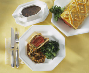 Beef Wellington, in puff pastry case on platter, served on dinner plate with spinach