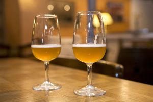 Belgium, Brussels, Musee Gueuze, two glasses of beer on table in Brasserie Cantillon