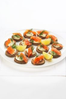 Blinis topped with smoked salmon, creme fraiche, dill and black pepper and garnished