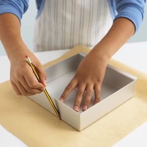 Boy using pencil to draw outline of box on wax paper