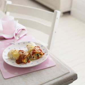 Chicken enchiladas on polka dot plate and place mat on table