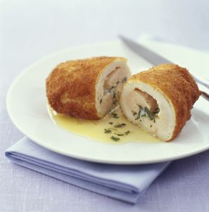 Chicken kiev cut in half revealing melting garlic and herb butter centre