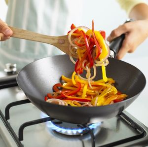 Child stirring sliced bell peppers and onions in frying pan using wooden spatula
