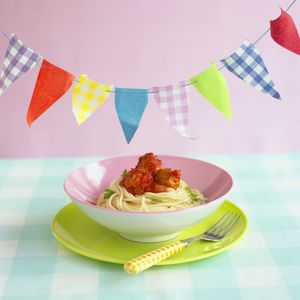 Childrens pasta bowl of chicken balls with spaghetti and tomato sauce with bunting above