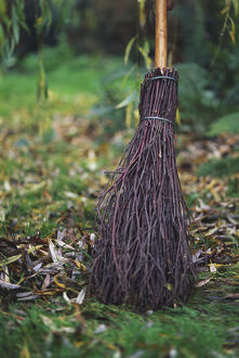 Close-up of a broomstick sweeping autumn leaves from a damp garden lawn