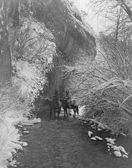 Two Crow Indians on horseback in shallow stream flanked by snow-covered trees, under
