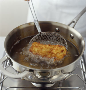 Deep frying chicken in shallow pan of oil