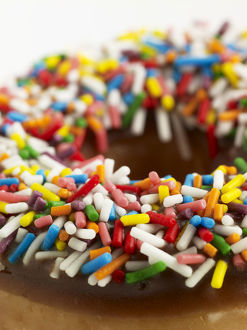 Doughnut with chocolate icing and colourful sprinkles, close-up