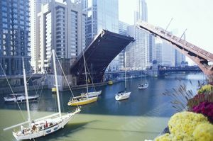 Drawbridge spanning the Chicago River opening for water traffic.