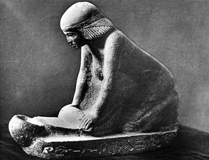 Egyptian woman grinding corn using a saddle quern. Egyptian tomb figure c 2,500 BC