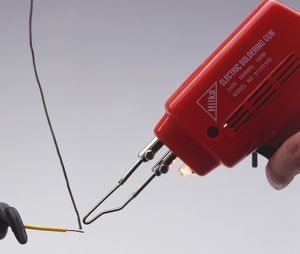 Electrical soldering iron with solder and copper wire.