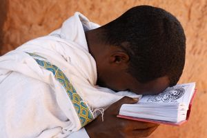 Faithful praying with a bible outside a church in Lalibela