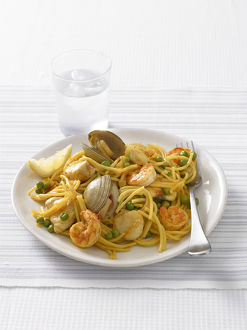 Fideua, a Spanish pasta dish of spaghetti, mixed seafood and peas, served with a glass of water