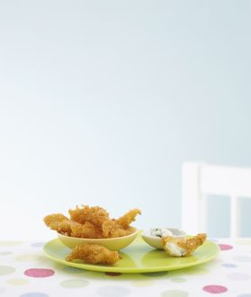 Fish goujons in bowl on plate with tartare sauce