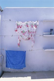 Flowered blouse hanging out to dry in the sun on a washing line