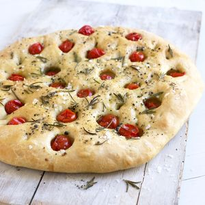 Focaccia bread topped with cherry tomatoes and sprigs of rosemary