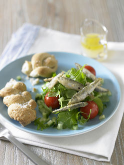 Fried whitebait on bed of green salad with tomato and bread rolls